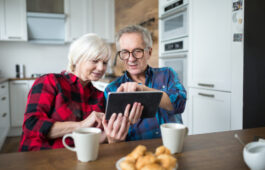 Portrait of senior couple using tablet at kitchen table